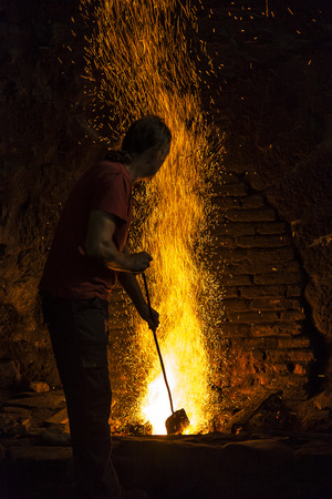 Blacksmith working in the fireplace of an old forge