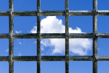 claustrophobic: Metal jail bars with a blue sky with some clouds in the background as a concept of freedom wish