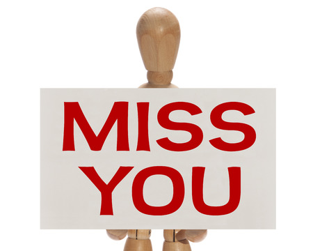 Wooden mannequin holding a white card with the message Miss you over a white background Stock Photo