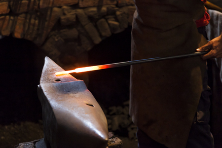 Blacksmith forging steel on the anvil in an old forge