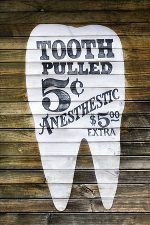 tooth extraction: Tooth extraction funny ad on a wooden wall