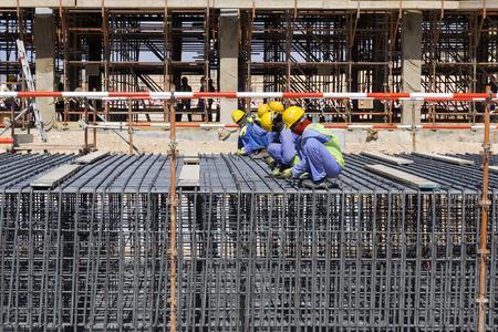 Ouvriers du bâtiment tricotant des barres d'armature pour des fondations en béton