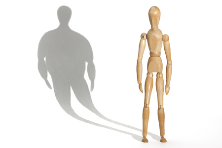 desease: Slender mannequin depressed because his distorted fat body shadow Stock Photo