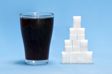 Sugar cubes with cola as a concept of too much sugar in the drink