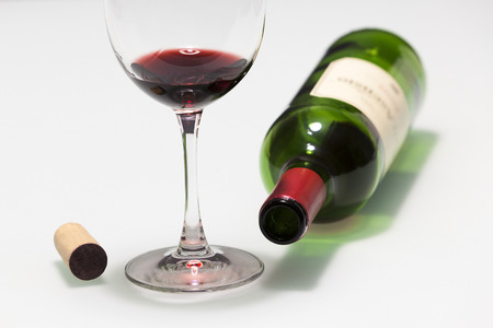 Cup with some red wine, cork and empty bottle