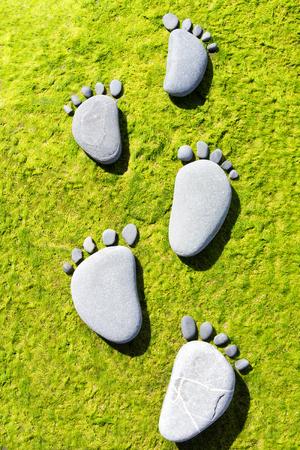Stone foot prints on green seaweed Stock Photo