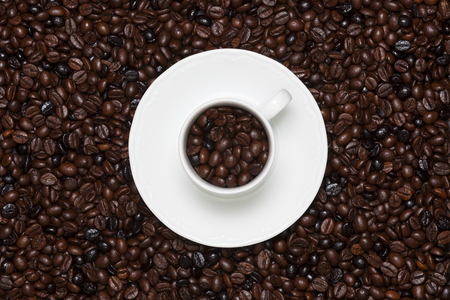 White cup with coffee grains inside and outside