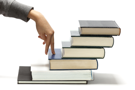 Fingers stepping on books, as a concept of the progress in education