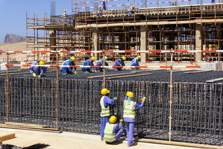 Construction workers preparing rebars for concrete foundation