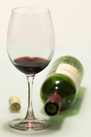 Cup with red wine, cork and empty bottle