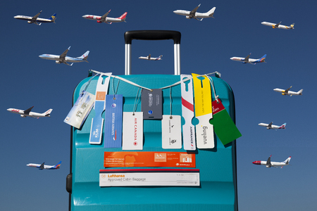 Trolley with hand luggage tags of different airlines over a blue sky with several airplanes Publikacyjne