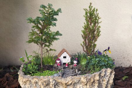 Outdoor fairy mini garden with dolls, trees and a small house