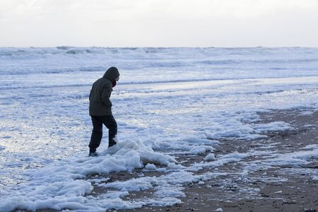 Man walking along a polluted beach