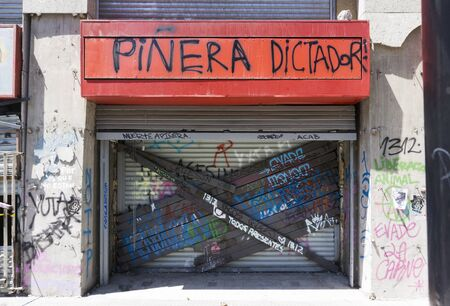 Damaged shop access in Santiago de Chile after the demostration, with grafitti and welded steel bars on the shutters to prevent looting
