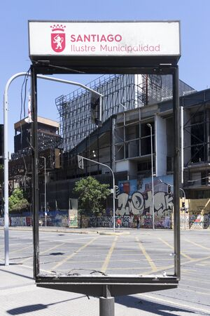 Ruined urban information panel in Santiago de Chile, after the demonstration against Piñera