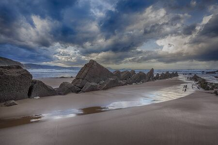 Low tide in the rocky beach of Sopela, Spain, at dusk