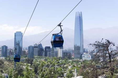 Santiago de Chile cityscape witj a cable car in the foreground. A view of modern buildings at the financial district popularly known as Sanhattan, in Las Condes district. The Costanera tower is the tallest skyscraper in South America Stock Photo