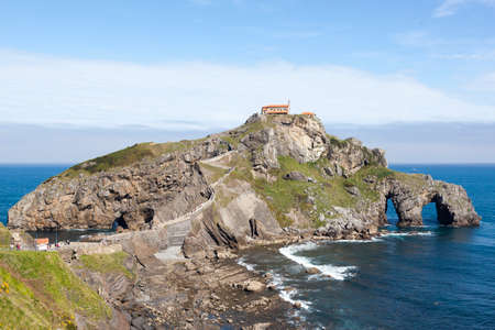 San Juan de Gaztelugatxe, Basque Country, Spain. It is an islet on the coast of Biscay, connected to the mainland by a man-made bridge. On top of the island stands a hermitage named Gaztelugatxe in Spanish, dedicated to John the Baptist, that dates from the 10th century. The hermitage is accessed by a narrow path, crossing a stone bridge, and going up 231 steps. According to legend, after the climb to the top of the crag one should ring the bell three times and make a wish. It appears as Dragonstone in the series Game of Thrones