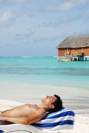 beautiful photo of a handsome man sunbathing at a Maldivian resort (ocean background) photo