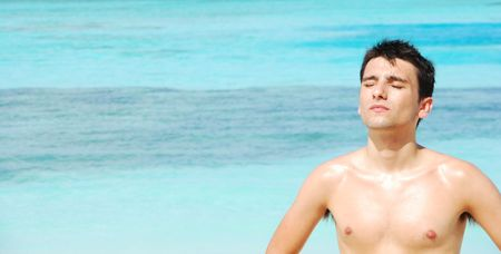 wide photo of a handsome man sunbathing at a tropical beach (ocean background) photo