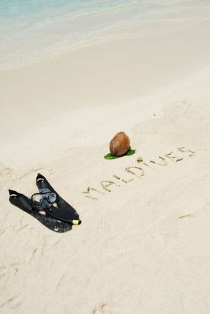 Maldives written in a sandy beach with coconut and snorkelling equipment photo