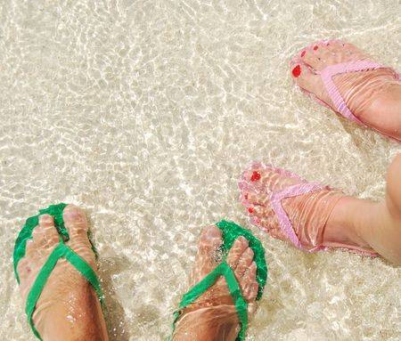 close up of feet and flip flops on a translucent ocean water photo