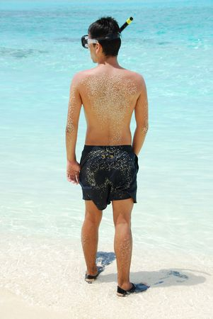 man getting ready to go snorkeling in a tropical island photo