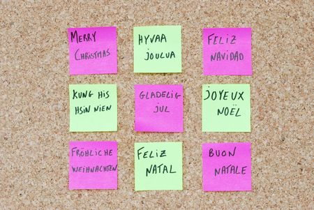 Merry Chritmas tree concept in nine languages with colorful post-it notes on a corkboard photo