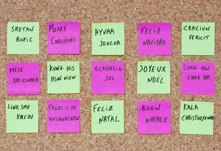 Merry Chritmas tree concept in fifteen languages with colorful post-it notes on a corkboard photo