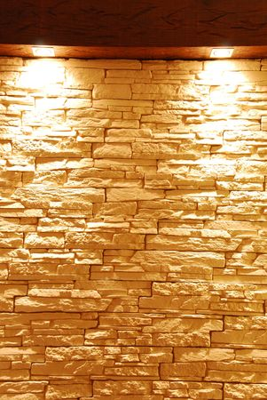 grey and unshaped stone wall with spot lights photo