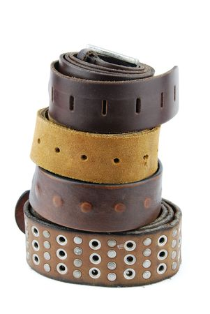 stack pile of leather belts isolated on white background photo