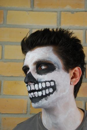portrait of a creepy skeleton guy perfect for Carnival (brick wall background)  photo