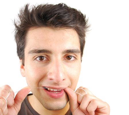 flossing: young man flossing his teeth isolated on white background