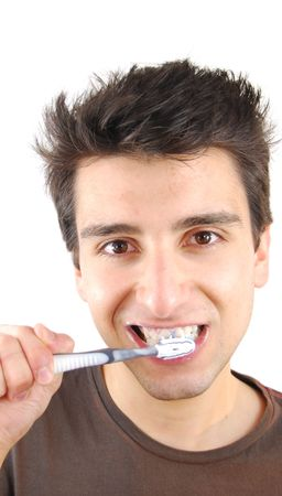 cheerful young man is washing teeth over white background  photo