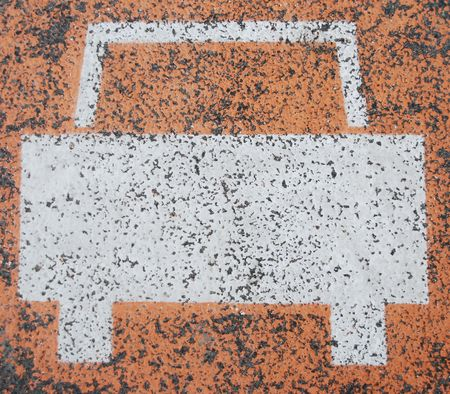 white car road sign painted on a orange asphalt surface photo