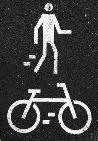 white pedestrian and bicycle road signs painted on the asphalt surface photo