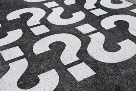 punto interrogativo: segni di punto interrogativo dipinti su una superficie di strada asfaltata