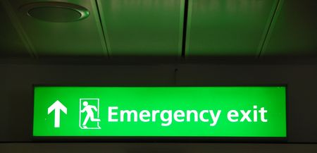 iluminate: green mergency sign at a international airport Stock Photo