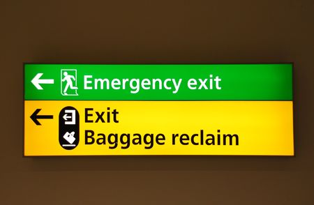 green emergency exit and yellow exitbaggage claim sign at a international airport photo