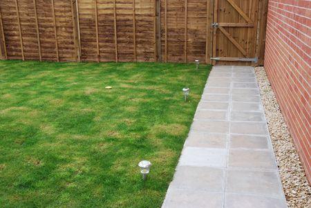 photocell: beautiful back yard garden (green grass, wood fencedoor, stone pavement, solar panel lights and brick wall) Stock Photo