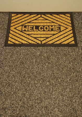 wiping: beautiful welcome home door mat on a grey carpet Stock Photo