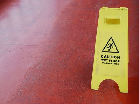 yellow caution sign regarding slippery surface (red pavement background) Stock Photo - 6914259