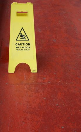 yellow caution sign regarding slippery surface (red pavement background) photo