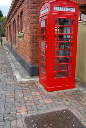 typical red telephone booth and brick wall building on the background Stock Photo - 6914399