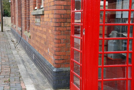 typical red telephone booth and brick wall building on the background photo