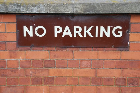 close-up of a no parking sign on a red brick wall  photo