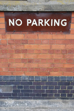 no parking sign on a red brick wall photo
