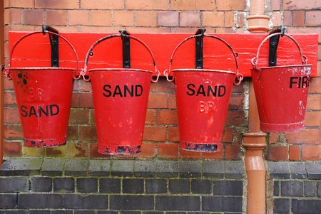 four antique fire buckets on hooks at a train station (brick wall background) photo