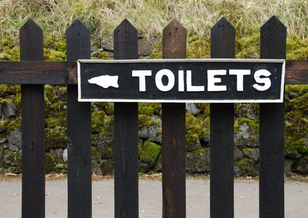 vintage toilets sign on wooden fence photo