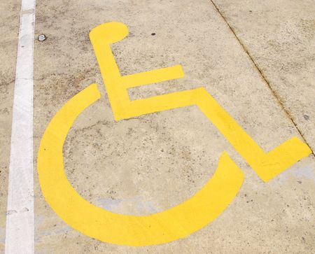 yellow wheelchair handicap road sign painted on a yellow pavement photo